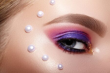 Closeup Macro of Woman Face with Purple and Pink Eyes Make-up with Perls Decor. Fashion Celebrate Makeup, Glowy Clean Skin, perfect Shapes of Brows. Shiny Simmer