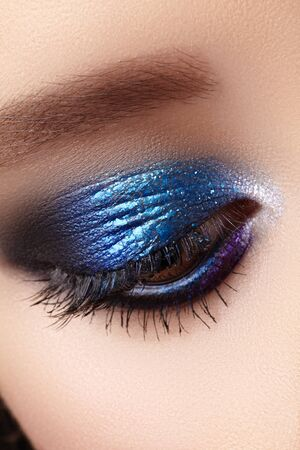 Closeup Macro of Woman Fashion Make-up of Eyes. Glitter Blue Celebrate Makeup, Perfect Color of Eyeshadows. Long Lashes.