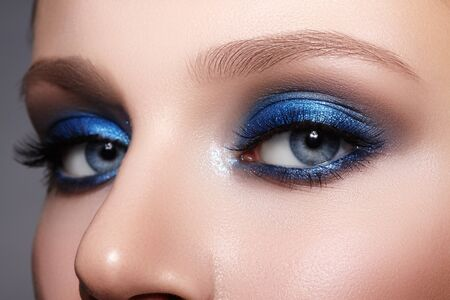 Closeup Macro of Woman Face with Blue Eyes Make-up. Fashion Celebrate Makeup, Glowy Clean Skin, perfect Shapes of Brows.