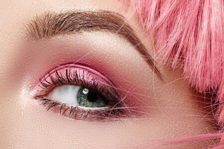 Closeup Macro of Pink Fashion Eye Make-up. Expressive Makeup, Bright Summer Eyeshadows and Magenta Color Hair, Shiny Skin