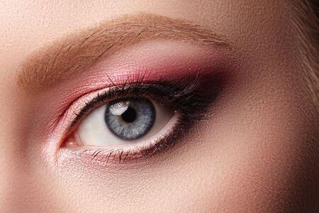 Nahaufnahme-Makro des Frauen-Gesichts mit Augen-Make-up. Mode feiert Make-up, strahlend saubere Haut und natürliche Augenbrauen. Sommerrosa und schwarze Lidschatten Standard-Bild
