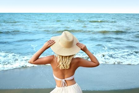 Blonde Woman in Fashion Summer Style Standing at Sea and Holding Hat. Luxury Lifestyle Rear View. Summer Vacation Concept with Ocean.