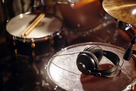Black Headphones on Studio Drums. Beautiful Closeup Concept of Recording Studio or Concert Hall Tools. Musical Background with Great Lights