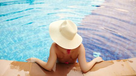 Relaxing on Beach Resort. Beautiful Back Side of Sexy Woman in big Hat Enjoying Vacation from Swimming Pool. Luxury Summer Traveling and Tourism Concept