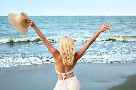 Blonde Woman in Fashion Summer Style Standing at Sea and Holding Hat. Luxury Lifestyle Rear View. Summer Vacation Concept with Ocean. Soul Relaxing, Spirit Calm