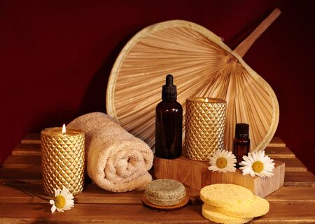 Beautiful Spa Composition. Aromatherapy with Herbal Oil, Natural Soap and Gold Candles. Relaxation Color and Warming Towels on Wooden Background