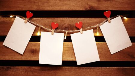 Blank White Piece of Paper hanging on Light Garland with Decorative Love Pins. Valentines Day Background with Copy Space. Cozy Wooden Background