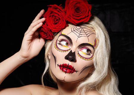 Beautiful Halloween Make-Up Style. Blond Model Wear Sugar Skull Makeup with Red Roses, pale Skin Tones and Waves Hair. Santa Muerte concept Reklamní fotografie