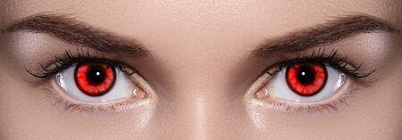 Close-up of Woman Eyes. Halloween Makeup. Devil, Vampire or Monster Eye Lens. Luminous Red Eyes. Closeup Shot