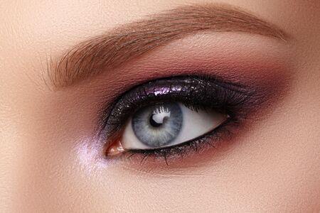 Hermoso maquillaje de ojos de primer plano con sombras de purpurina púrpura. Maquillaje de celebración de moda, piel limpia y radiante, formas perfectas de cejas. Brillo brillante