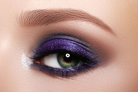 Closeup Macro of Woman Face with Purple Eyes Make-up. Fashion Celebrate Makeup, Glowy Clean Skin, perfect Shapes of Brows. Shiny Simmer Zdjęcie Seryjne