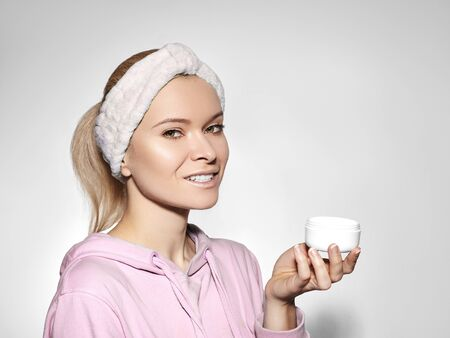 Happy woman with perfect skin applying day-night cream on cleansed face. Good concept of skincare, beauty industry, spa center and facial treatment Foto de archivo