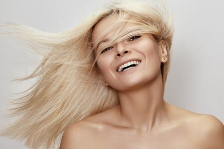 Beautiful woman with magnificent blond hair. Happy model face with windswept flying hair. Shiny long health hairstyle. Beauty and haircare Foto de archivo