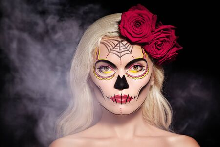 Beautiful Halloween Make-Up Style. Blond Model Wear Sugar Skull Makeup with Red Roses, pale Skin Tones and Waves Hair. Dia de los Muertos or Day of the Dead or Santa Muerte concept Foto de archivo