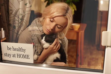 Be Healthy, Stay Home. Woman blonde in home clothing in apartment with cute cat in her arms stay at home. Self isolating while quarantine concept. Stop virus