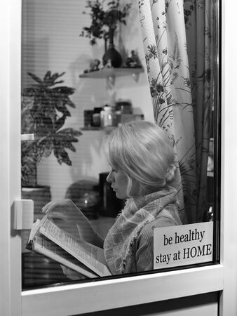 Education and rest at home. Be Healthy, Stay Home. Blond woman reads book. Self isolating while quarantine concept Foto de archivo