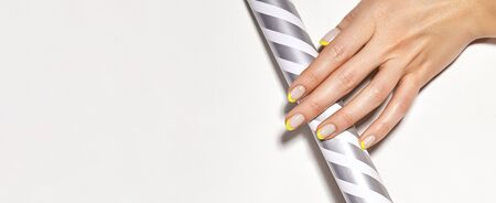 Hands with bright yellow french manicure on geometric background. Nails art design. Close-up of female hands with trendy neon nails on silver striped print tube. Copy space Foto de archivo