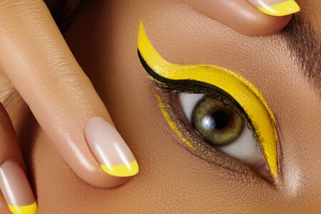 Bellissimo macro primo piano dell'occhio femminile con trucco eyeliner giallo brillante. Trucco Neon Disco e Fashion Manicure. Stile di bellezza estivaRipresa macro del primo piano del viso degli occhi della fodera di moda