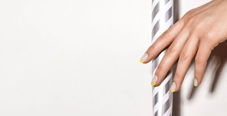 Hands with bright yellow french manicure on geometric background. Nails art design. Close-up of female hands with trendy neon nails on silver striped print tube