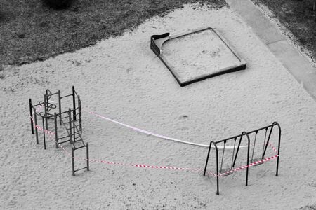 Playground equipment is closed due to Covid-19. Top view of Uninhabited place during a pandemic. Red stop ribbon on teeter. Stay at home