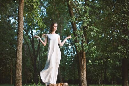 Beautiful Woman Posing like Goddess in White Long Dress at Nature. Boho Style, Spirit Calm, Wellness and Self-making. Freedom and Relaxing. Soul Health Foto de archivo