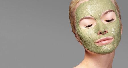 Beautiful Woman Applying Green Facial Mask. Beauty Treatments. Close-up Portrait of Spa Girl Apply Clay Facial mask on grey background Foto de archivo