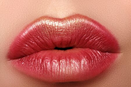 Macro close-up glamour fashion bright red lips make-up with gold glitter. Macro of woman's face part. Sexy lip makeup, luxury visage