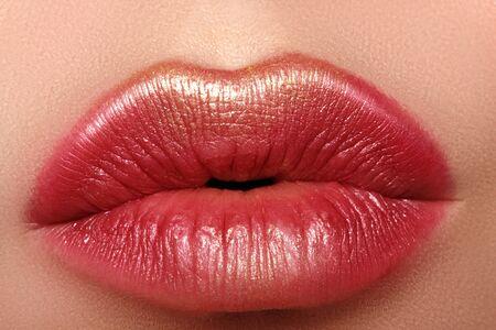 Makro Nahaufnahme Glamour Mode leuchtend rote Lippen Make-up mit Goldglitter. Makro des Gesichtsteils der Frau. Sexy Lippen-Make-up, luxuriöses Gesicht