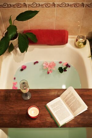 Time for Yourself. Relax at home. Bath tub with flower petals. Book, candles and glass of wine on a wood tray. Organic Spa Relaxation in comfort cozy bathroom