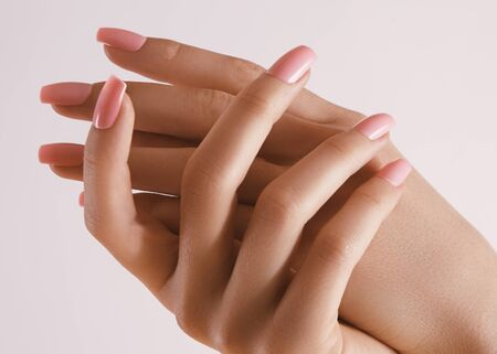 Beautiful Woman Hands. Soft skin, skincare concept. Hand Skin Care. Female Hands Applying Cream or Lotion. Spa and Manicure concept. Female hands with tender pink manicure
