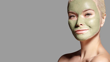 Beautiful Woman Applying Green Facial Mask. Beauty Treatments. Close-up Portrait of Spa Girl Apply Clay Facial mask on grey background. Archivio Fotografico