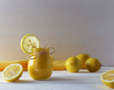 Homemade Lemon Curd made from eggs, lemon, butter and honey, in a glass jar on a white wooden background Stock fotó