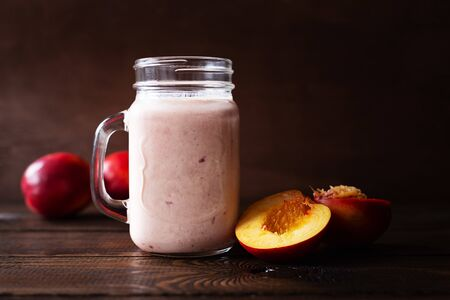 Nectarine smoothie in glass and fruit on dark wooden background.