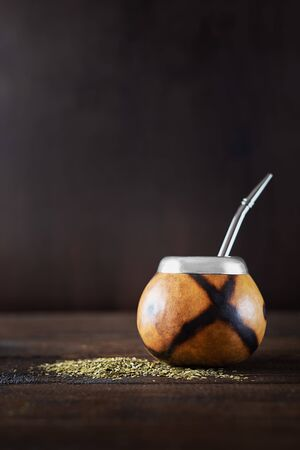 Dried mate tea leaves, high in caffeine, Calabasas and bombilla on a dark wooden background