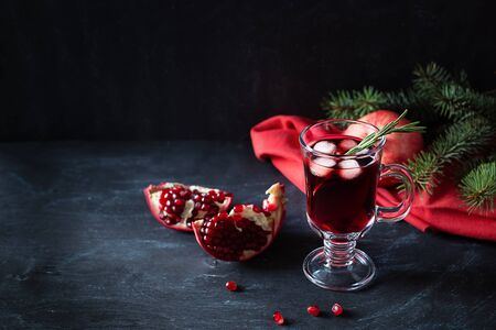 Pomegranate Christmas cocktail with rosemary, champagne, club soda on black table. Xmas drink. Close up. Copy space. Horizontal orientation.