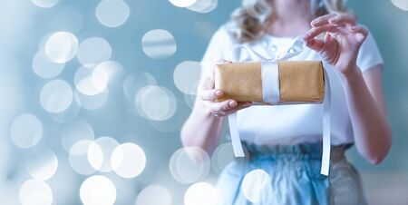 The womans hands open the gift box. Blue background with flickering light bokeh. Valentines day, birthday concept.