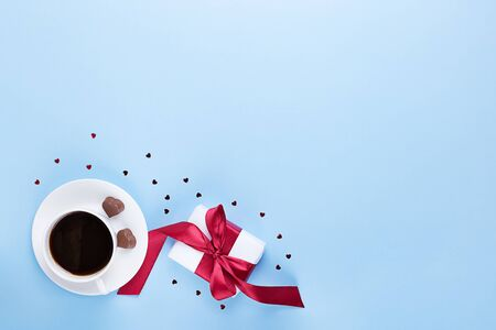 Festive banner of Valentines Day. A Cup of coffee, a gift box and a heart-shaped chocolate on a blue background. Flat lay. Top view. 스톡 콘텐츠
