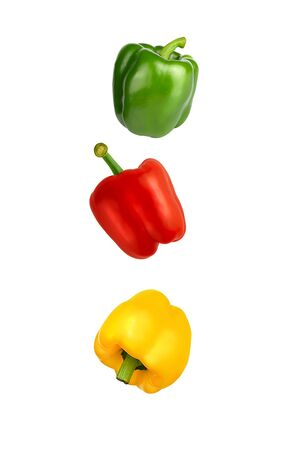 Falling red, yellow and green Bulgarian sweet peppers isolated on white background with clipping path. Flying vegetables.