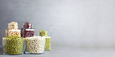Bowls and jars of various legumes: chickpeas, lentils, mung, red and white bean on a gray background with copy space. Banner.
