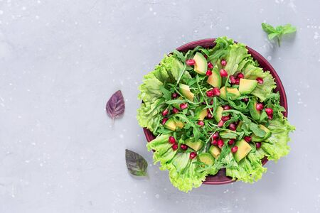 Avocado and pomegranate salad in a clay plate on a gray background. Healthy food. Top view. Stockfoto