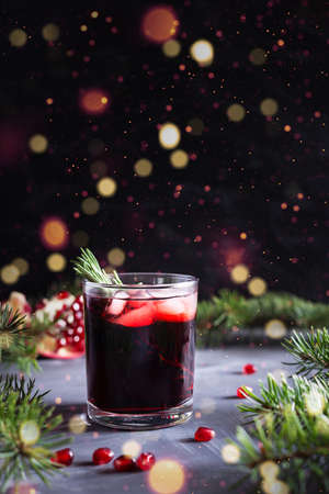 Pomegranate Christmas cocktail with rosemary, champagne, club soda on black table with bokeh lights. New year drink