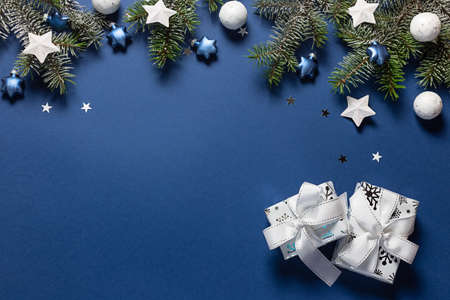 Christmas snowy border of gift box, shiny balls and stars, evergreen branches on blue background. New Year card