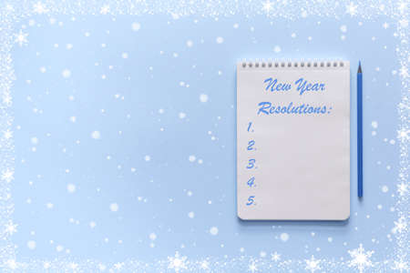 Notebook with a list of new year's resolutions with a pencil for writing on a blue Christmas background with snowflakes. Planning concept. Top view, copy space, mock up. Stock Photo
