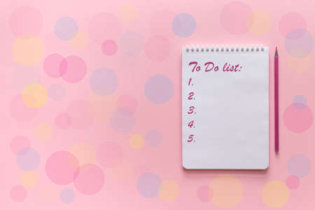 Notebook with to do list with a pencil for writing on a pink background with festive colorful bokeh. Planning concept. Top view, copy space, mock up. Stock Photo