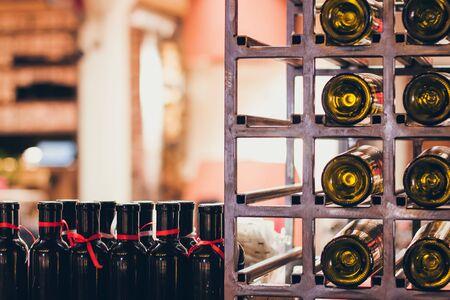 Closeup shot of wine shelf. Bottles lay over straw. Wine cellar