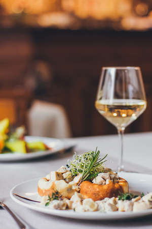 Stuffed mushrooms filled with cheese, mushroom stem and microgreen on the white plate with a glass of wine