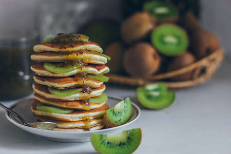 Plate of pancakes dripping with kiwi jam with kiwi pieces. Shrovetide Maslenitsa Butter Week festival meal. Shrove Tuesday. Pancake day. 스톡 콘텐츠