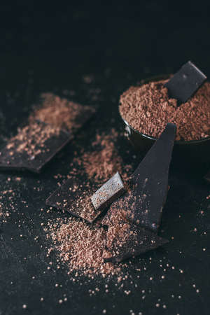 Chocolate bar pieces with cocoa powder on dark background, cope space 免版税图像