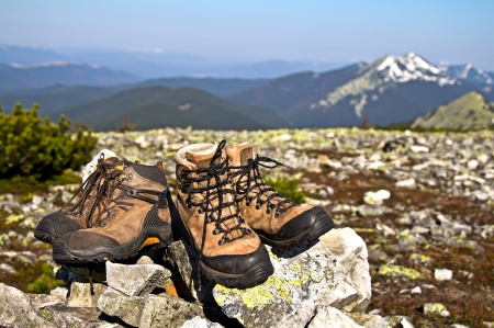 Old used boots against of mountain landscape