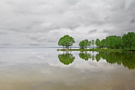 Green trees reflected in the lake surface under the cloudy sky
